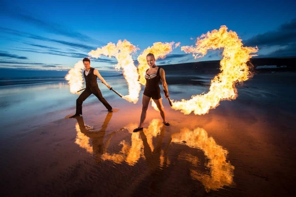 Blaze Fire Dancers performing a fire show on a beach in the UK. Our fire dancers are available to book for events in the UK.