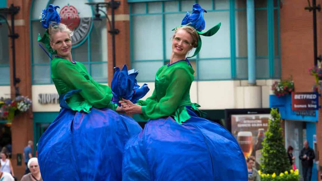Flower Stilt Walkers performing at a shopping centre in the UK.