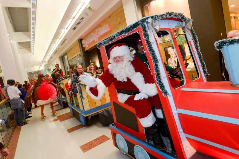 Santa Claus performer driving our red Christmas Land Train around a UK shopping centre.