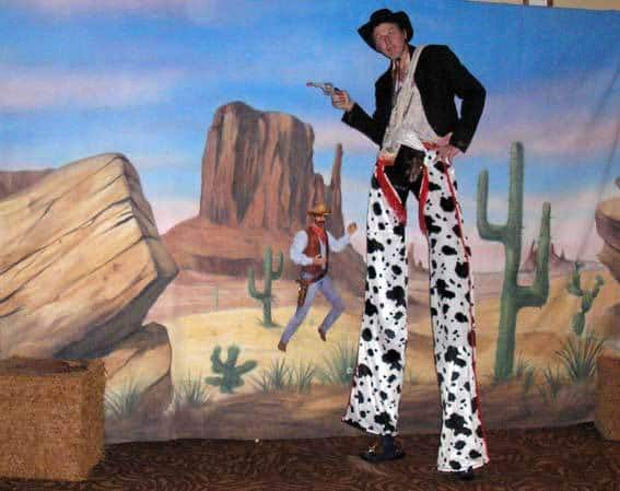 Cowboy Stilt Walker standing in front of a wild west desert backdrop. Our wild west-themed entertainment is available to book for family fun days, carnivals, summer festivals or corporate events in London & the UK.
