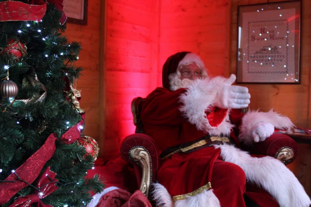 Santa Claus performer in a Father Christmas Chair next to a bespoke Christmas Tree inside our Santa Grotto. We fully produced and managed this newmarket Christmas event.