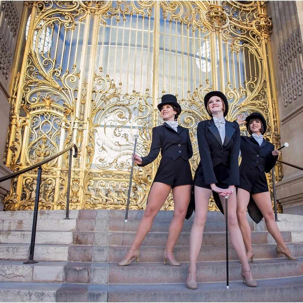 1920s themed Gatsby dancers in front of a large golden gate.