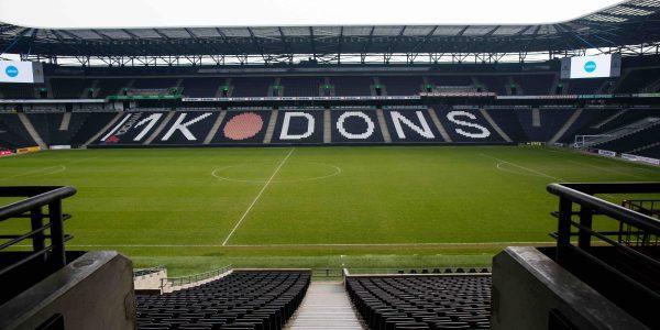 Inside the MK Dons Stadium. MK Dons logo on stadium bleechers.