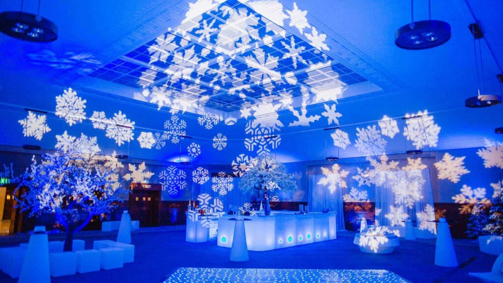 White snowflakes projected over blue lit venue space for winter wonderland event theming for Christmas party