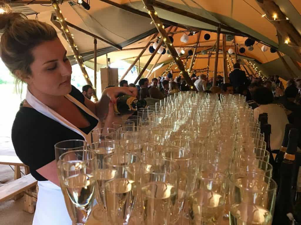 Champagne glasses covering a pallet bar inside a large festival marquee.