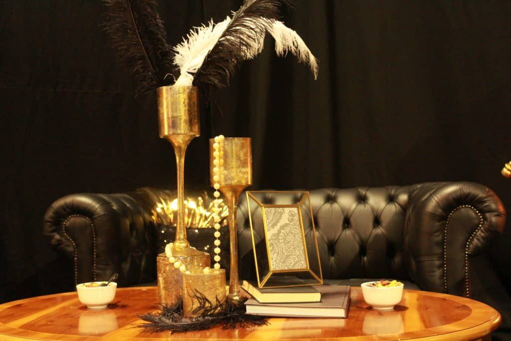 White and black feathers in gold cups used as a 1920s themed table centrepiece.