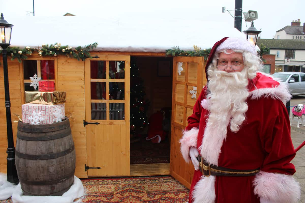 Our Santa performer standing outside this bespoke Santa's grotto