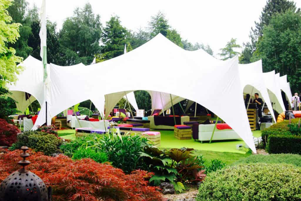 Private Peastock festival party created in our client's back garden. Featuring a large white marquee and bright multi-coloured drapings.
