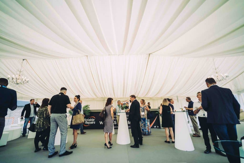 Group of delegates in marquee tent that we provided full event cleaning services including using better air to purify this event spaces air. Our event cleaning solutions were used to ensure the space stay clean and safe for delegates