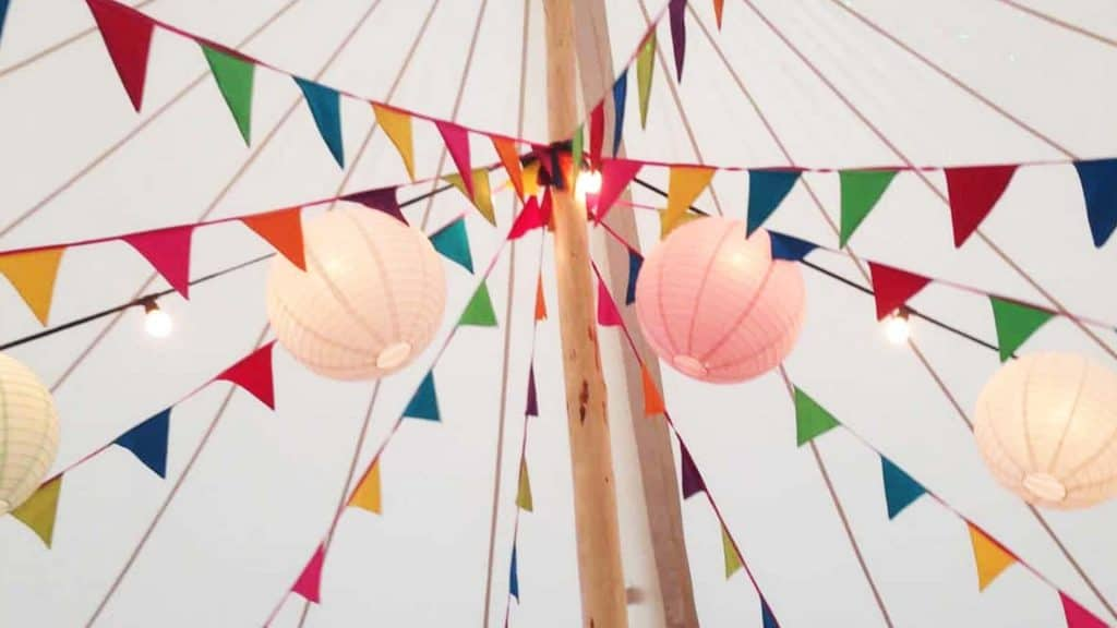 Multi-coloured Easter Bunting Decorations tied to a wooden post in a white marquee.