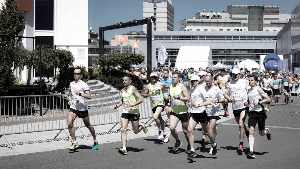 Group of Marathon Runners running down a paved street.