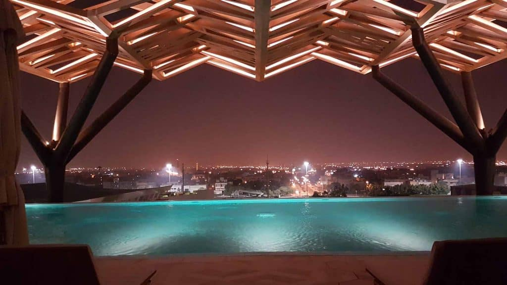 Kuwait 4 Seasons Hotel rooftop swimming pool at night.