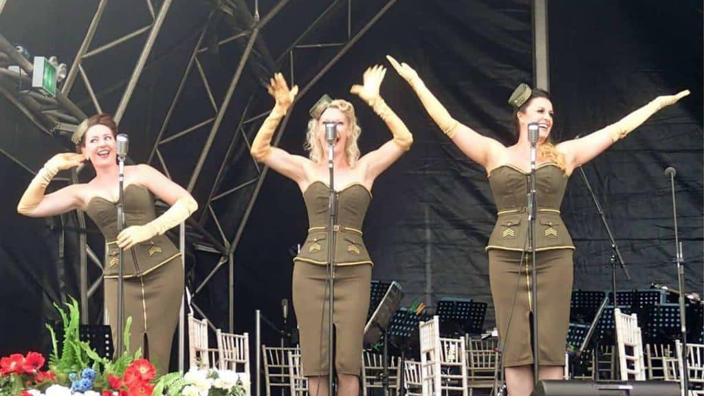 Vintage 1940's style girl group, singing on stage in vintage military style outfits.