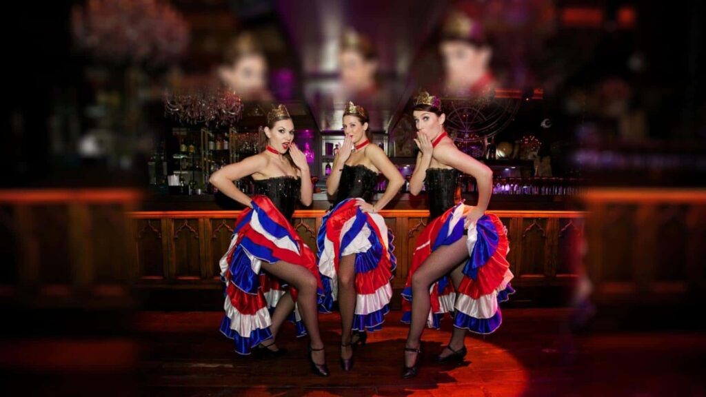 Cabaret style Can Can Dancer trio dressed in black tops with red, blue and white dance skirts.