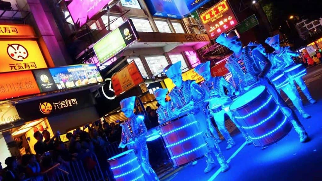 Futuristic glow band performing in street parade in front of big crowds.