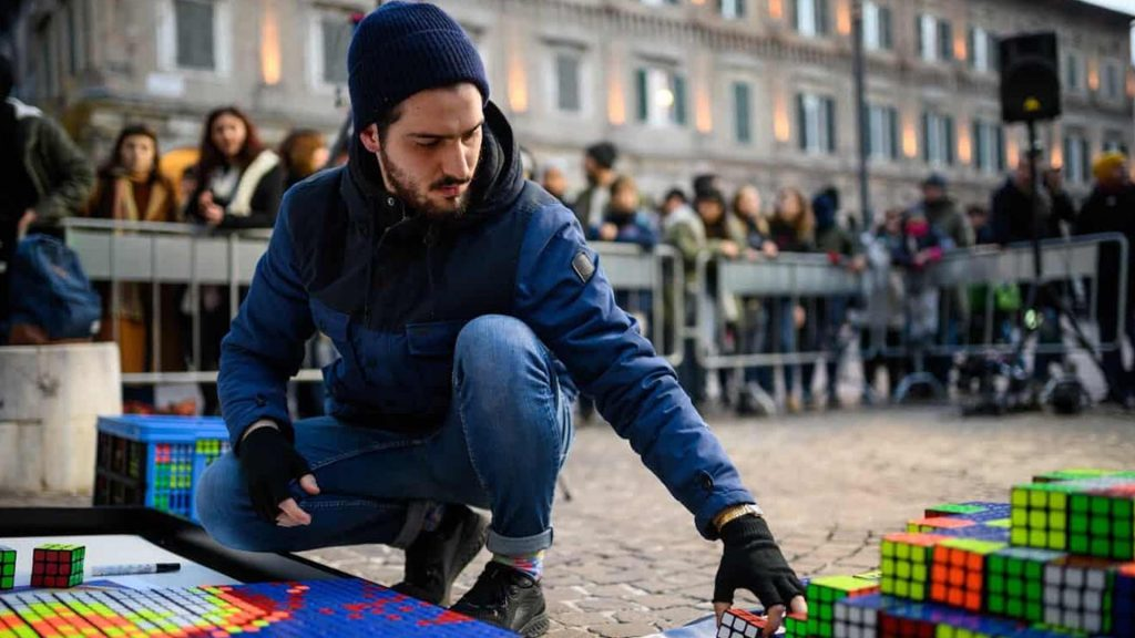Jvenb Giovanni Contardi creating Rubik's Cube portrait in front of a crowd.