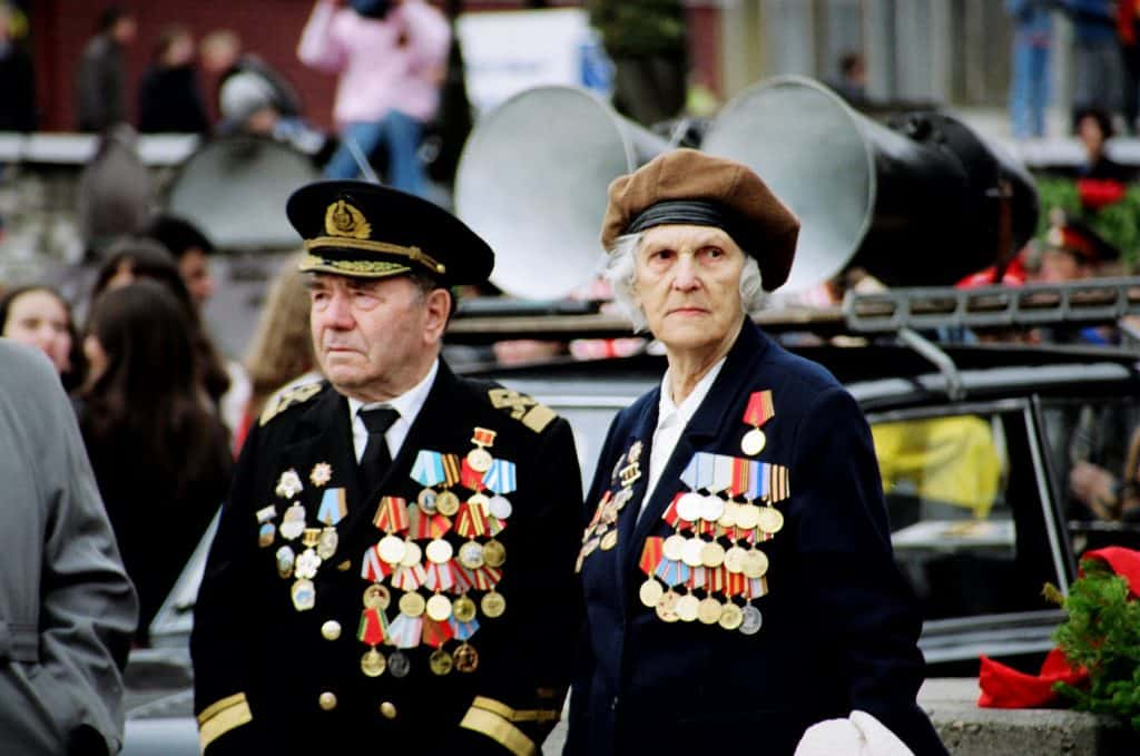 Male and Female War Veterans wearing lots of medals at commemorative service to remember  the sacrifices they and their comrades made in World War 2