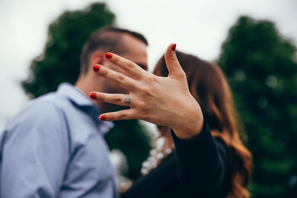 Women showing engagement ring to camera after being proposed too. Kissing partner in background.