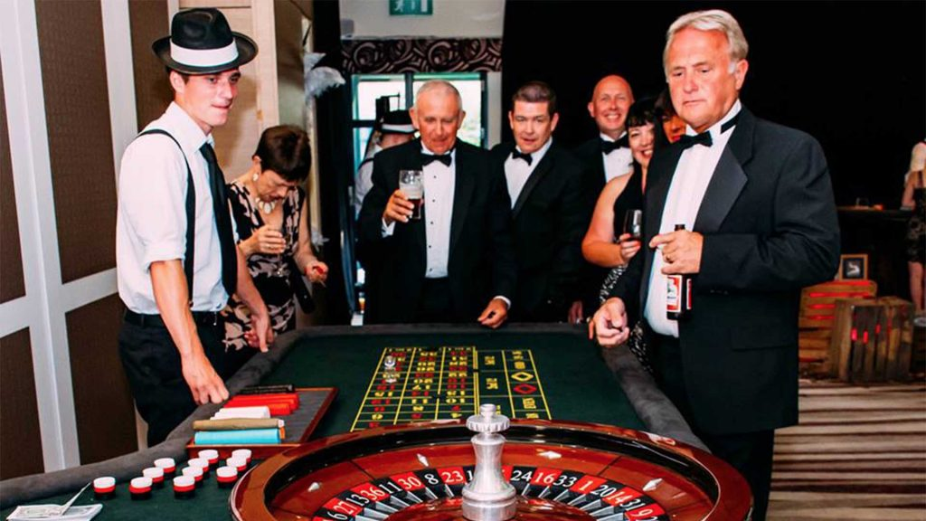 Men in tuxedos gathered round a roulette table hired for Las Vegas and Casino Themed Event