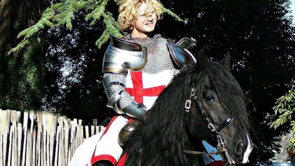 St.George with English flag on armour sat on large black horse. Available as part of medieval entertainment to hire London UK
