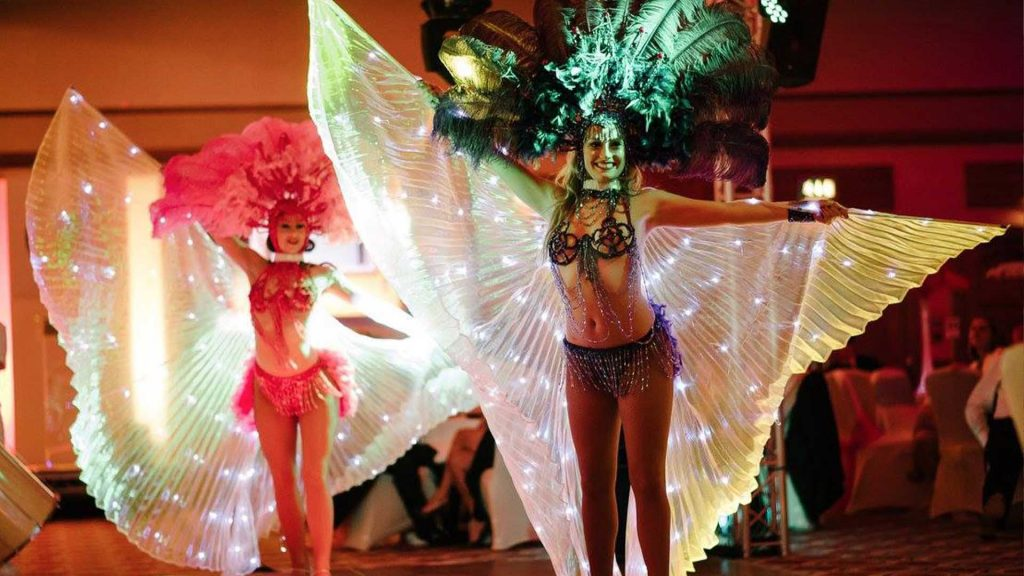 Vegas showgirls with light up wings performing in front of guests at Las Vegas Themed Gala Dinner. Available to hire London UK