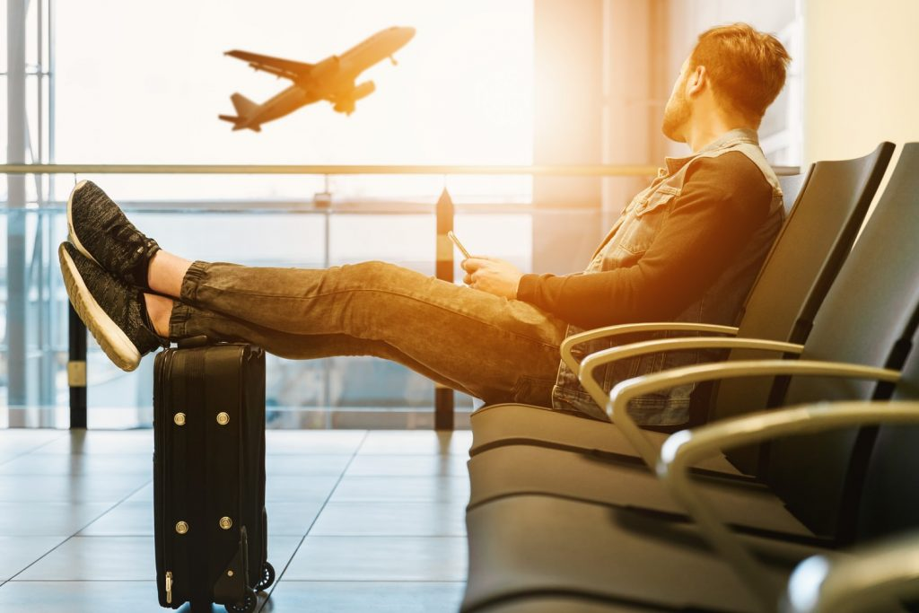Young man from an Events Agency sitting on an airport seat in an airport terminal watching a plane tack off in front of the sun.