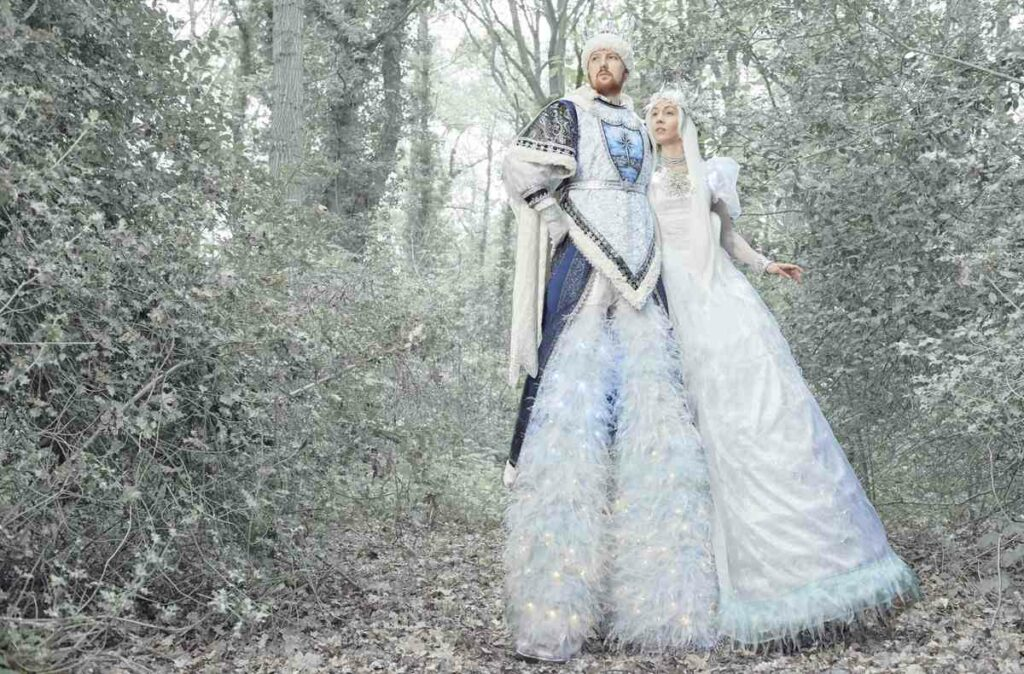 Ice King and Ice Queen Stilt Walker Pair in a Snowy Forest.
