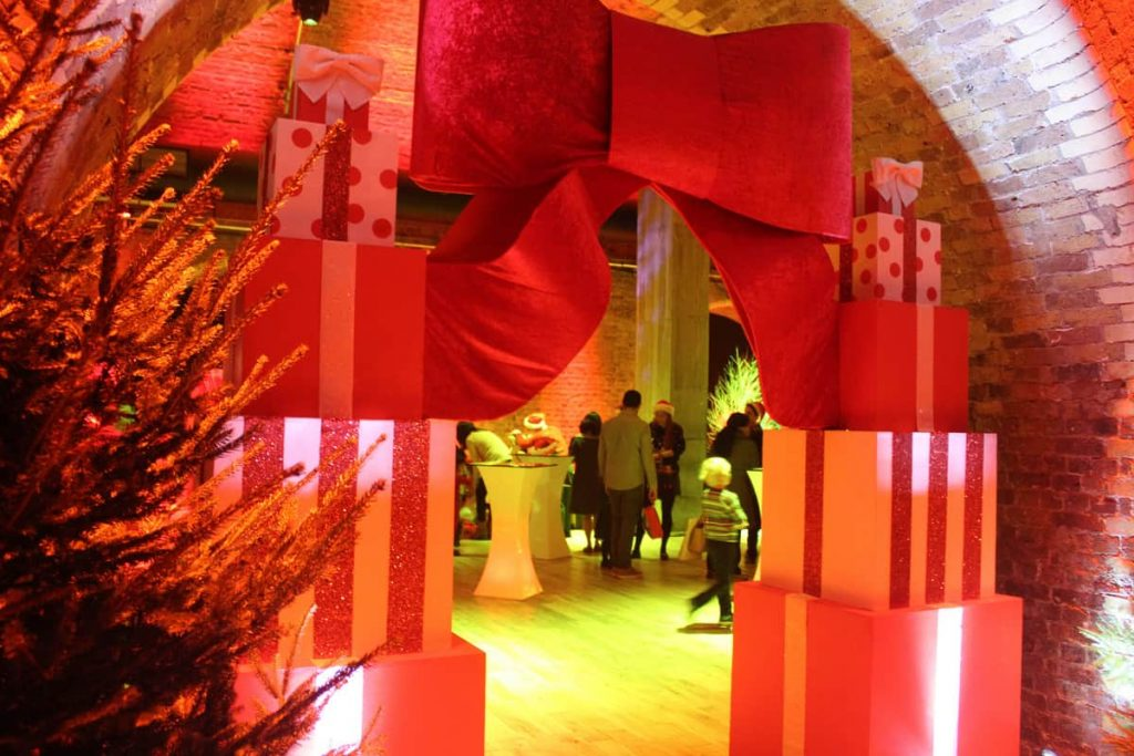 Giant Christmas present archway and Christmas trees surrounding the entrance to a corporate Christmas party as part of our Christmas event theming.