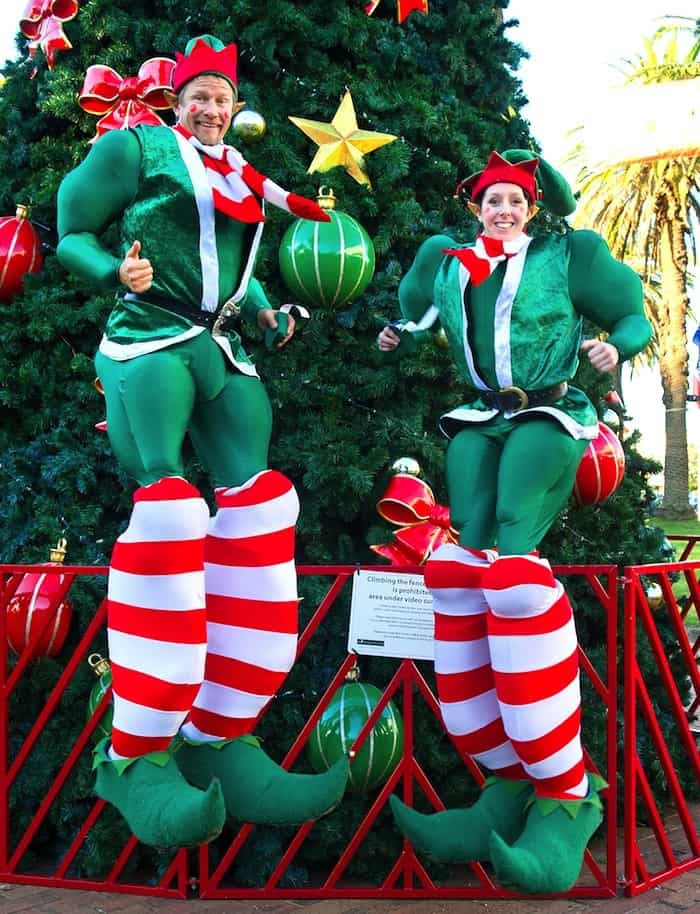 Bouncing Elf Stilt Walkers standing in front of a large Christmas Tree at a Santa Grotto event in a Garden Centre in the UK.