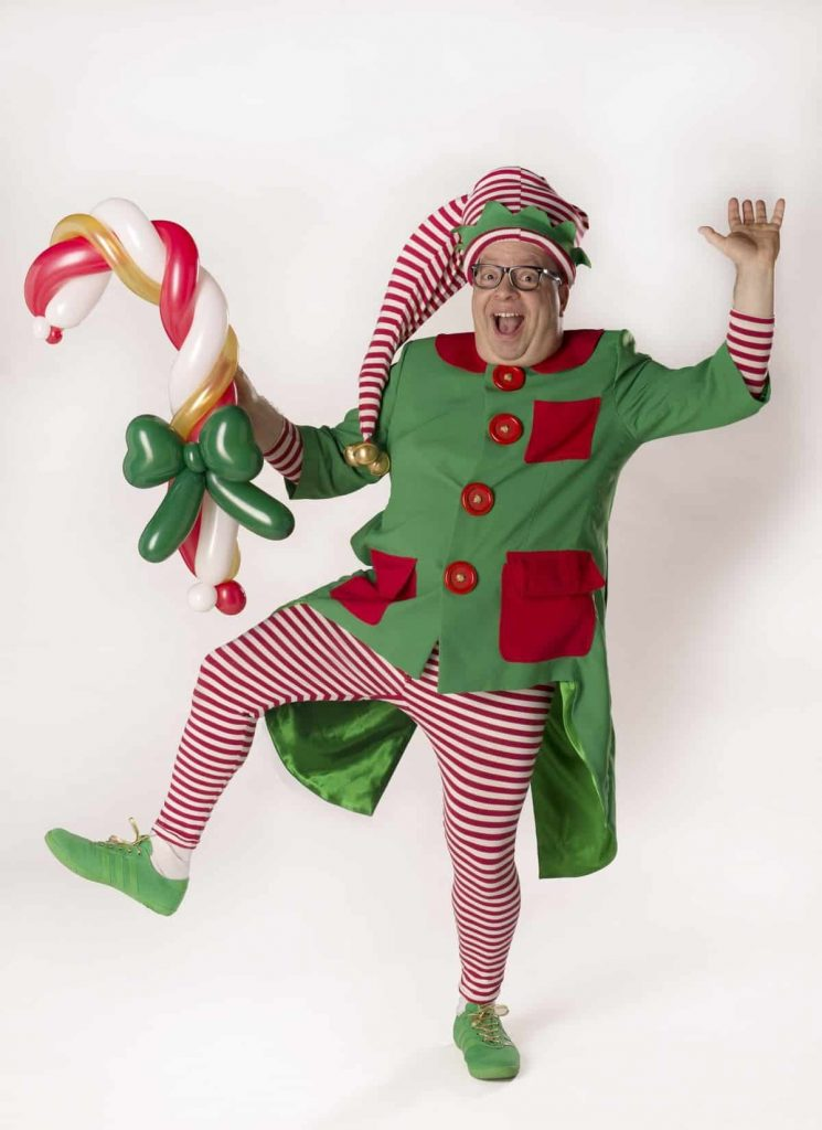 Christmas Elf Balloon Modeller with a Candy Cane created from green, white, gold and red balloons. This unique elf performer is available to book for Christmas Events across the UK and Worldwide.