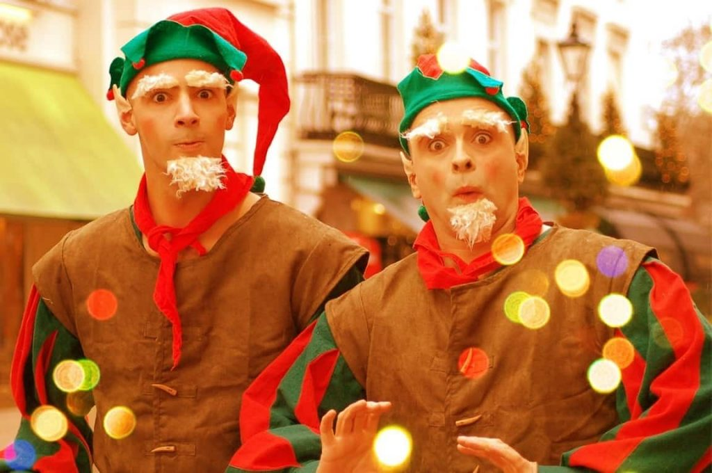 Comedy Elves performing at a Christmas Street parade event in the UK. This Elf Duo wear bespoke elf costumes with red and green colours and interact with your guests.