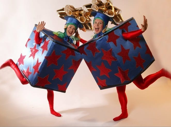 Gift Box Elves wearing their bespoke blue and red present outfits. Our Christmas Elves are available for hire across the UK, join us as we explore our favourite Elf performer options.