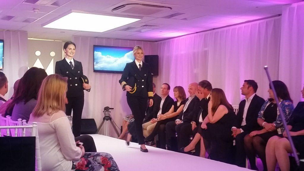 Monarch fashion show event we produce using our fashion show event production services. Two female models showcasing new pilot uniform down catwalk.