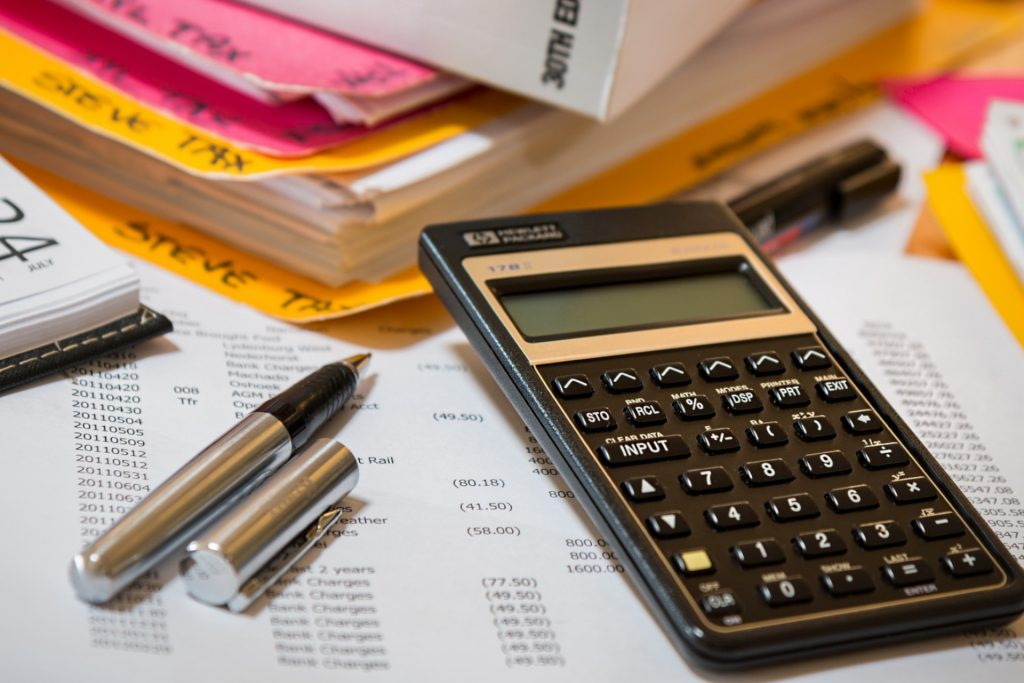 Calculator, pen and budget lists used by event manager London to plan out event costing