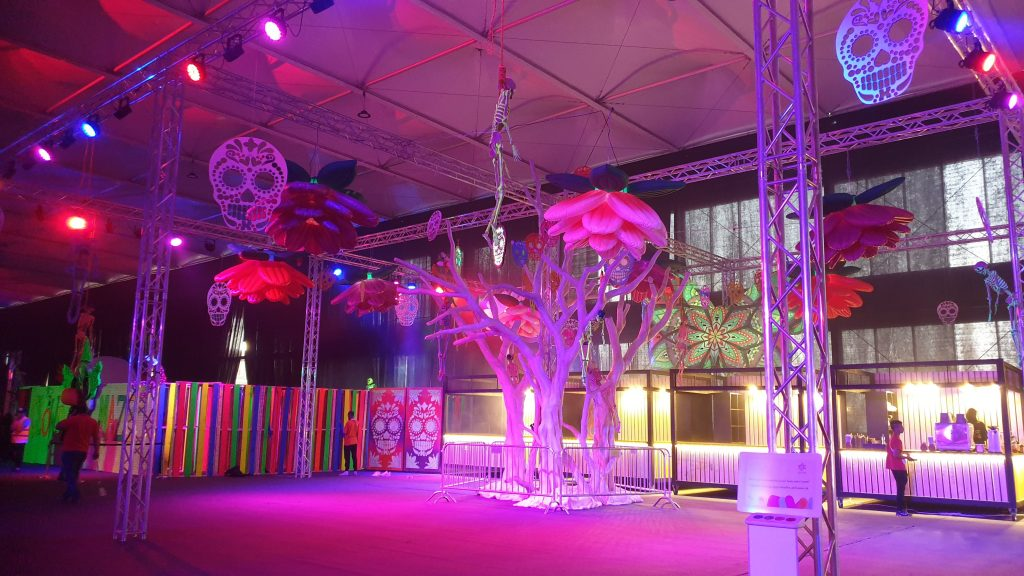 Day of the dead themed area for Saudi Arabia Horror Festival event featuring giant trees and sugar skulls