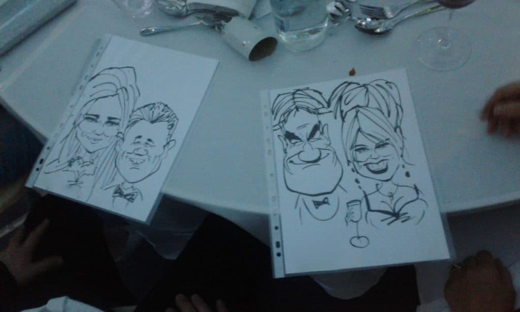 Table with wine and two caricatures of the guests in a coporate party