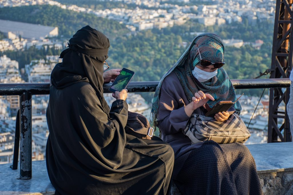 Saudi women wearing different clothing options including full burqa, abaya and head scarf.