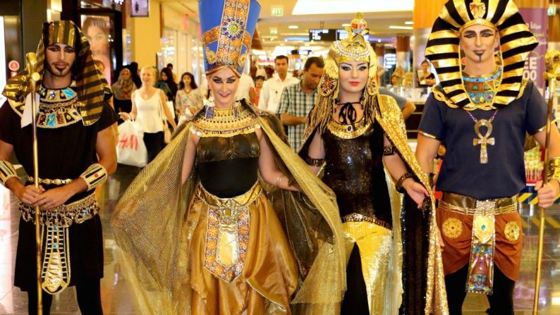 Egyptian performers crew dressed in gold roaming a shopping centre curated by entertainment organisers providing entertainment shows for hire