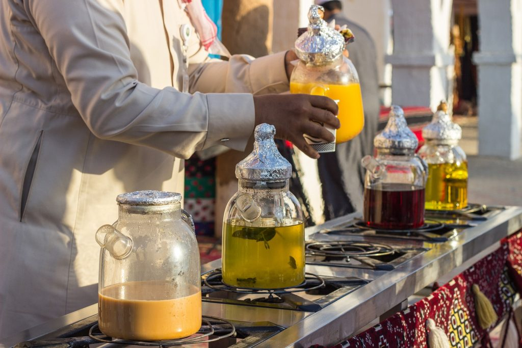 Man serving different kinds of teas and drinks in Saudi Arabian restaurant.