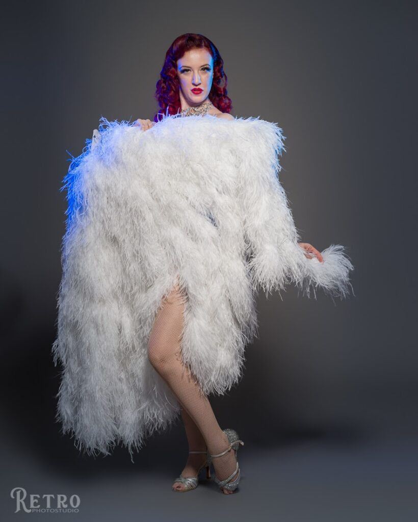 Burlesque dancer Belle Burlesque holding covering herself in large white feather cover at the start of burlesque performance