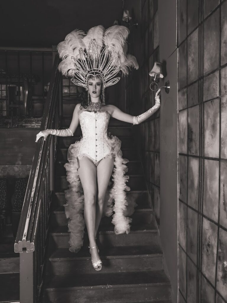 Belle Burlesque wearing white corset and feather headdress for burlesque showgirl performance