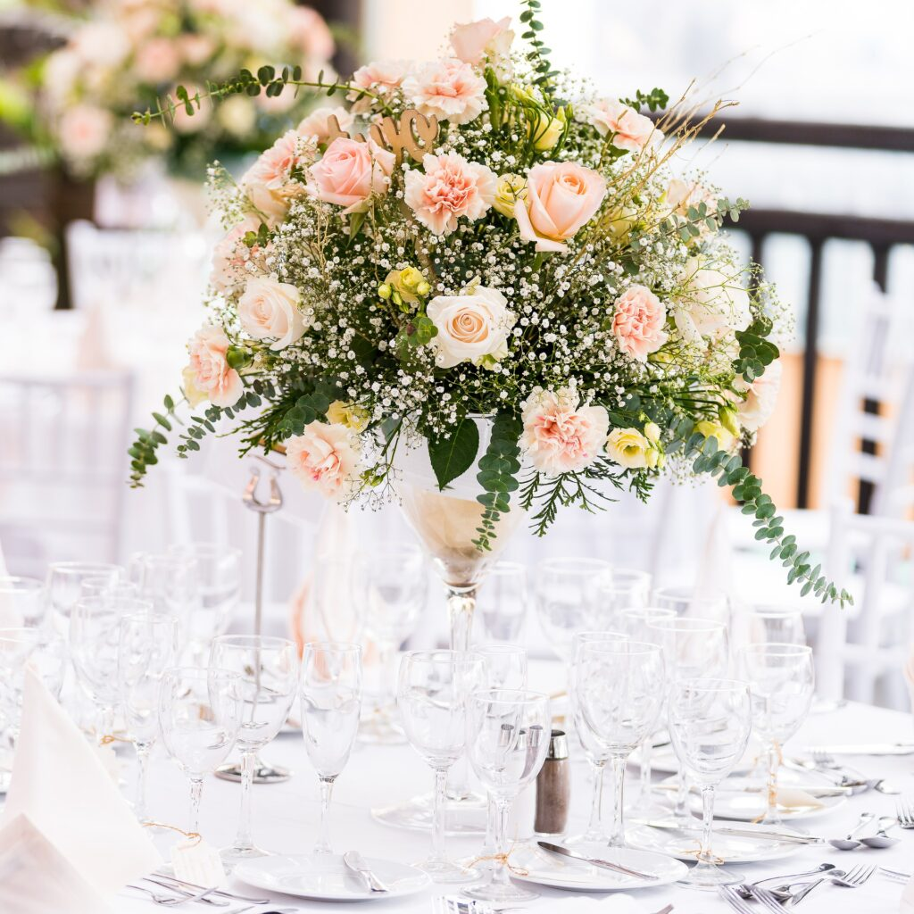 Tall floral wedding table centrepiece full of roses and eucalyptus in centre of table at outdoor wedding.
