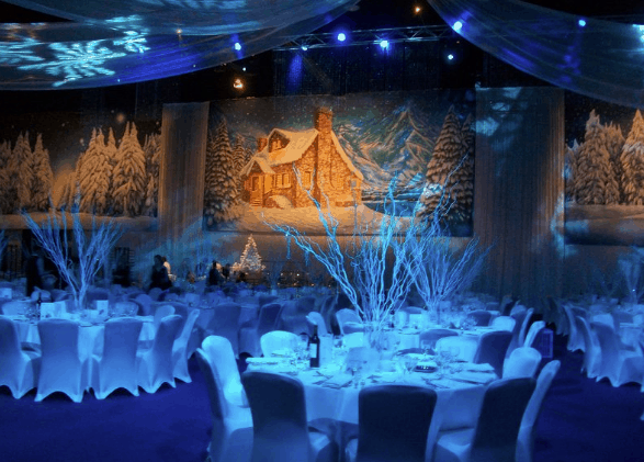 White venue draping and Christmas themed backdrop used to decorate venue space for winter wonderland party.