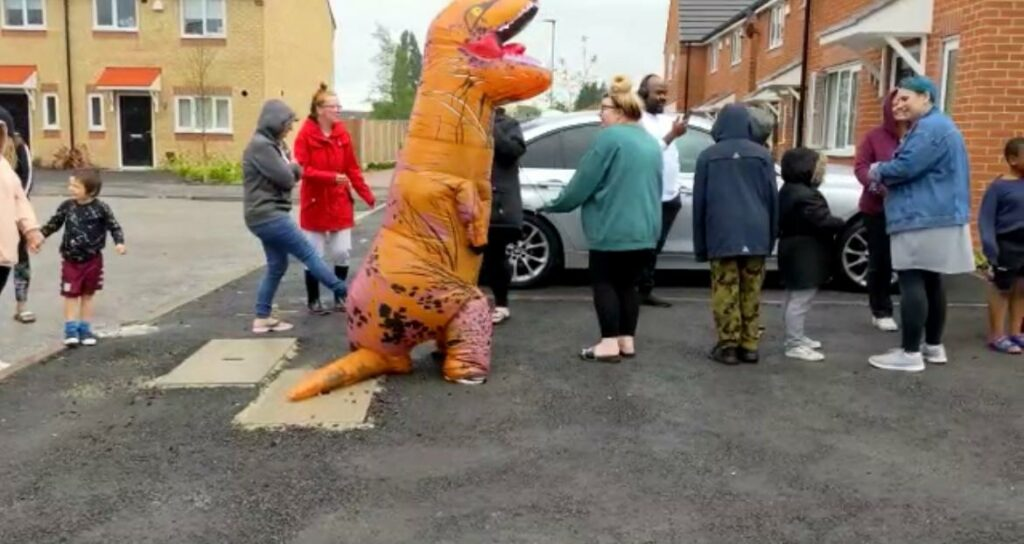 Tenant in a T-Rex costume lined up to collect her ice cream at simple life ice cream community event.